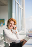 Businesswoman talking over mobile phone. Executive businesswoman talking over mobile or smart phone with her partners, colleagues or friends. Red haired lady Stock Photography