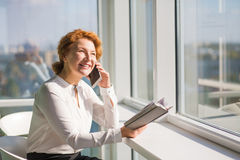 Businesswoman talking over mobile phone. Happy confident businesswoman talking over mobile or smart phone and looking at window. Red haired lady communicating Royalty Free Stock Image