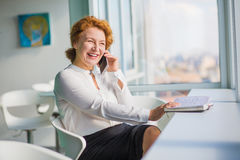 Businesswoman talking over mobile phone. Happy smiling businesswoman looking at window while talking over mobile or smart phone with friends or closed relatives Royalty Free Stock Images