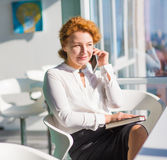 Businesswoman talking over mobile phone. Portrait of red haired businesswoman talking over mobile or smart phone and looking at window while discussing plans for Royalty Free Stock Photo