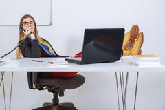 Businesswoman talking over the phone. Business woman in her office talking over the phone Stock Photography