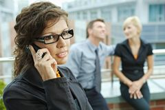Businesswoman talking on phone. Business people talking on terrace outdoor of office building. Businesswoman in front using mobile phone Royalty Free Stock Photo