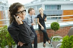 Businesswoman talking on phone. Business people talking on terrace outdoor of office building. Businesswoman in front using mobile phone Royalty Free Stock Photography