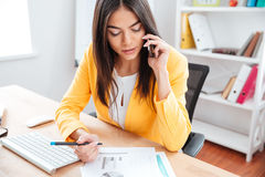 Businesswoman talking on the phone and analysing graphics. On the paper in office Stock Photography