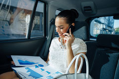 Businesswoman talking on the phone in the back seat of the Royalty Free Stock Photos