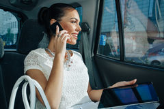 Businesswoman talking on the phone in the back seat of the Royalty Free Stock Photo