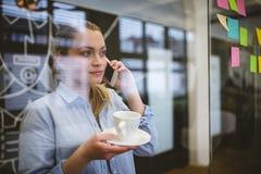 Businesswoman talking on phone during coffee break Royalty Free Stock Photo