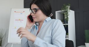 Businesswoman talking on phone while working at office stock footage