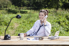 Businesswoman talking on the phone and drinking coffee Stock Photo