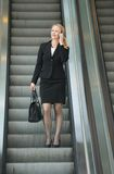 Businesswoman talking on phone on escalator Stock Photography