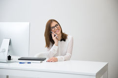 Businesswoman talking on the phone at her workplace Stock Photography