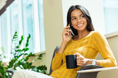 Businesswoman talking on the phone and holding cup with coffee Royalty Free Stock Image