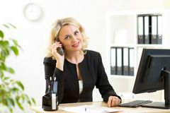 Businesswoman talking on phone in office Royalty Free Stock Images
