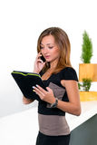 Businesswoman talking on the phone in office and holding the tablet with a list of tasks. Business concept of office work. Royalty Free Stock Photos