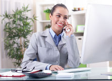 Businesswoman talking on the phone in office and working on comp Stock Photography