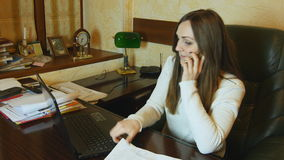 Businesswoman talking on phone and reads the document and working on laptop in her office stock video footage