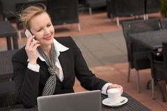 Businesswoman talking on the phone while relaxing outdoors with laptop and cup of coffee Stock Photo