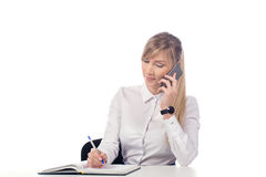 Businesswoman talking on the phone and taking notes. Woman sitting at the table and taking notes on the phone. isolate Stock Photos