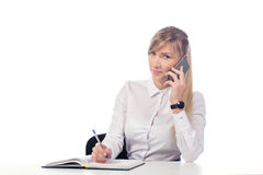 Businesswoman talking on the phone and taking notes. Woman sitting at the table and taking notes on the phone. isolate Stock Images