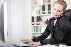 Businesswoman Talking on Phone Typing on Computer Royalty Free Stock Photos