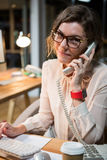 Businesswoman talking on phone while working on computer at her desk Stock Photo