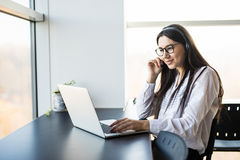 Businesswoman talking on the phone while working on her computer Royalty Free Stock Photography