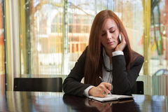 Businesswoman talking on the phone. And writes something in a notebook Royalty Free Stock Photos