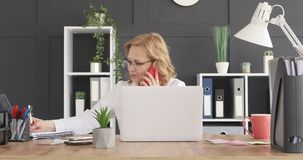 Businesswoman talking on phone and writing notes stock footage