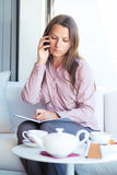 Businesswoman talking on the phone and writing in organizer in a Stock Photos