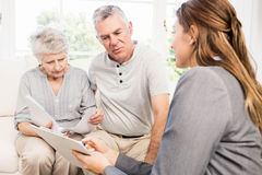 Businesswoman talking with senior couple and showing clipboard Royalty Free Stock Photos
