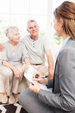 Businesswoman talking with senior couple and writing on clipboard Stock Image