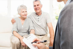Businesswoman talking with senior couple and writing on clipboard Royalty Free Stock Images