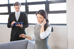 Businesswoman talking on smartphone and businessman using digital tablet Royalty Free Stock Photos