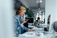 Businesswoman talking on smartphone and looking at documents. Young female executive sitting in front of pc Royalty Free Stock Photo