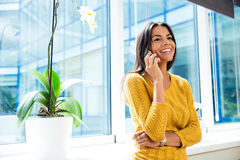 Businesswoman talking on smartphone in office Royalty Free Stock Image