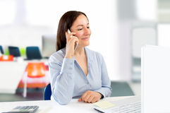 Businesswoman talking by smartphone at the office Royalty Free Stock Photo