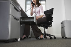 Businesswoman Talking On Telephone While Opening Drawer In Offic Stock Photo