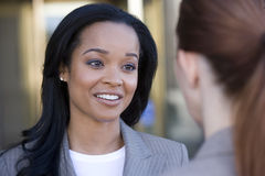 Businesswoman talking to colleague, smiling, close-up (differential focus) Stock Photography