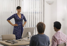 Businesswoman talking to male colleagues behind desk in office, hand on hips, smiling Royalty Free Stock Photo