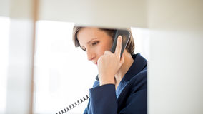 Businesswoman Talking to Someone Using Telephone Royalty Free Stock Images