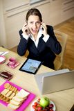 Businesswoman talking with two phones Royalty Free Stock Photography