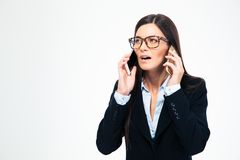 Businesswoman talking on two phones Royalty Free Stock Image