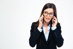 Businesswoman talking on two phones Royalty Free Stock Images