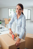 Businesswoman taping up a cardboard box Stock Image