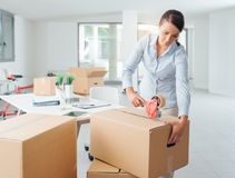 Businesswoman taping up a cardboard box Stock Photos