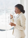 Businesswoman with tea cup looking through office window Royalty Free Stock Image