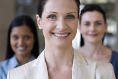 Businesswoman with team behind Royalty Free Stock Images