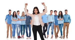 Businesswoman team leader celebrating victory with her group. Businesswoman team leader celebrating victory with both hands in the air, with her young casual stock photos