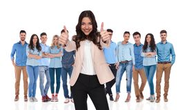 Businesswoman team leader making ok sign while standing in front. Smiling businesswoman team leader making ok sign while standing in front of her young casual royalty free stock photos