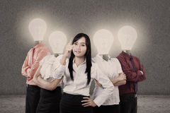 Businesswoman and team with light bulb heads. Showing strong business team royalty free stock photography